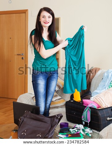 Smiling brunette woman choosing dress for vacation