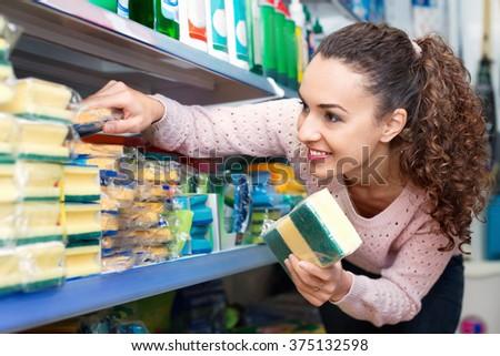 Smiling brunette woman choosing sponges in household section of supermarket - stock photo