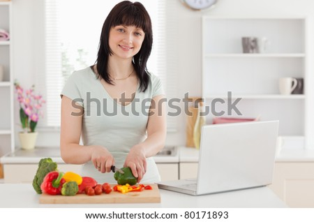 Smiling brunette woman cooking while relaxing with her laptop in the kitchen
