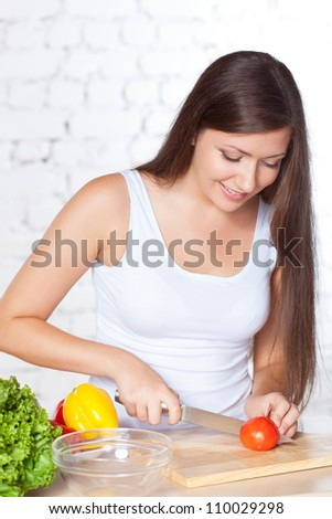 smiling brunette woman cutting  fresh tomato over white brick wall