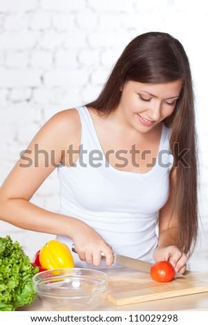 smiling brunette woman cutting  fresh tomato over white brick wall - stock photo