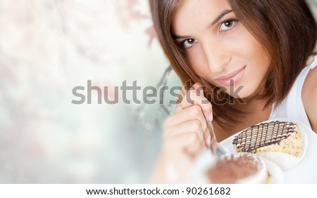 Smiling brunette woman eating some cake in the living room in her apartment - stock photo