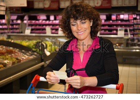 Smiling Brunette woman holding receipt in supermarket