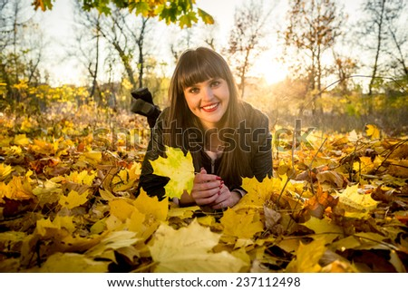 Smiling brunette woman lying on ground covered with leaves at autumn park - stock photo
