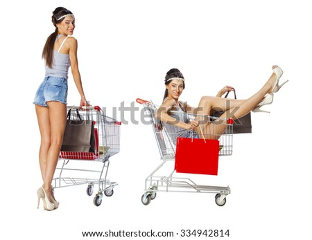 Smiling brunette woman posing next to an empty shopping cart isolated on white background - stock photo