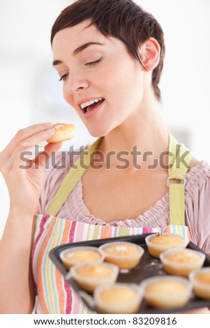 Smiling brunette woman showing muffins while eating one in a kitchen - stock photo