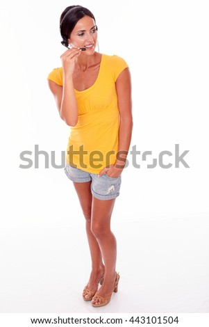 Smiling brunette woman touching the microphone and one hand in her pocket while looking away wearing a yellow t-shirt and short jeans isolated