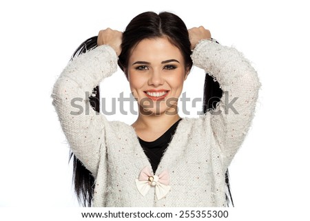Smiling brunette young woman holding two ponytails.  Gorgeous white caucasian female model feeling happy about her healthy hair. - stock photo