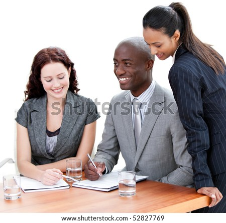 Smiling business co-workers studying a document in a meeting