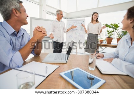 Smiling business colleagues conducting presentation in the office - stock photo