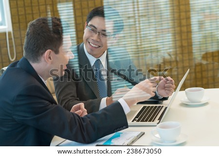 Smiling business colleagues discussing strategy in the meeting room - stock photo