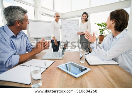 Smiling business colleagues ending presentation in the office - stock photo