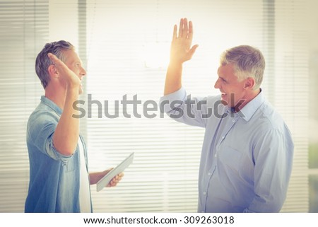 Smiling business colleagues giving high-five at the office - stock photo