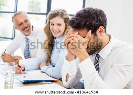 Smiling business colleagues looking at frustrated man in office
