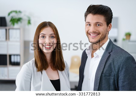 smiling business colleagues standing at the office and looking at camera