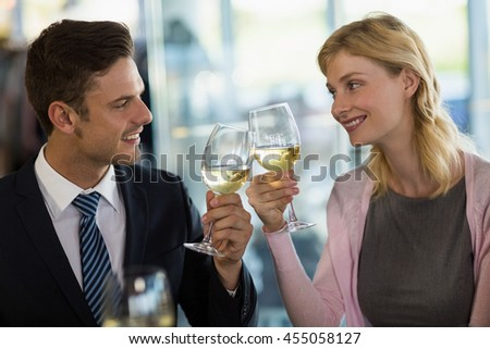 Smiling business colleagues toasting beer glass in a restaurant