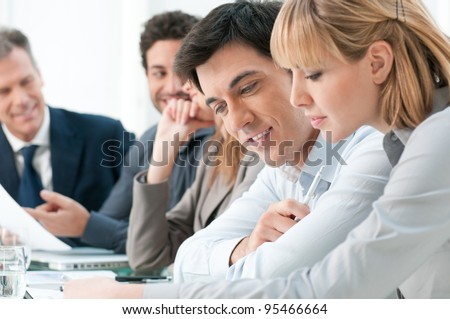 Smiling business colleagues working together during a meeting in office - stock photo