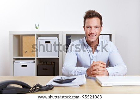 Smiling business consultant in office at desk