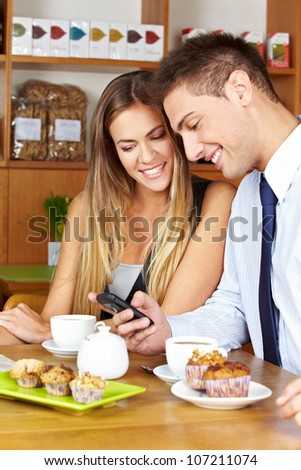 Smiling business couple with smartphone sitting in a caf�© - stock photo