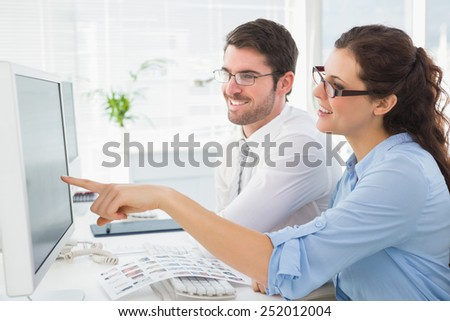 Smiling business coworkers pointing screen of computer in the office - stock photo