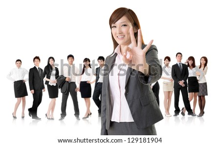 Smiling business executive woman of Asian give you an okay sign in front of her team isolated on white background. - stock photo