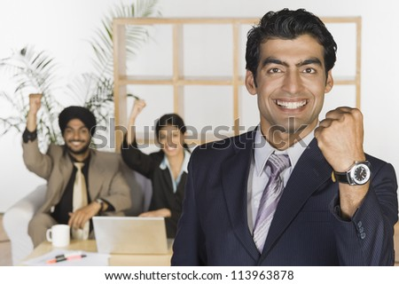 Smiling business executives showing fist and smiling - stock photo
