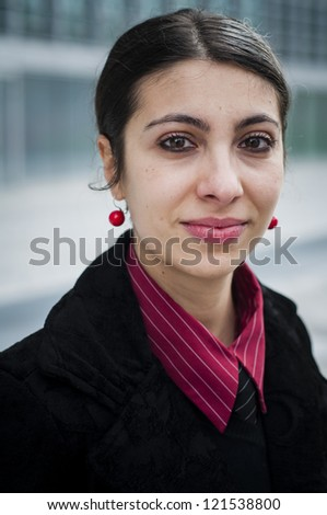 smiling business girl in front of a modern building - stock photo