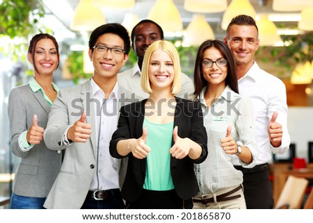 Smiling business group giving thumbs up - stock photo