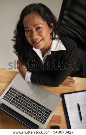 Smiling business lady sitting at her workplace and looking at camera, view from above