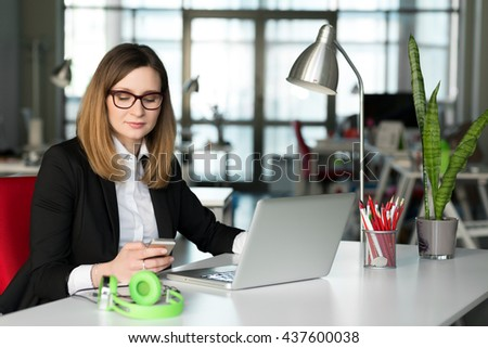 Smiling Business Lady using Telephone and Computer in official clothing black Jacket and white Shirt at grey Table with Laptop and other Gadgets in contemporary digital Office - stock photo