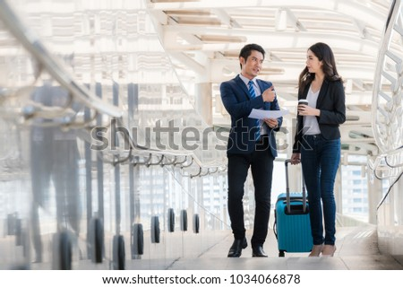 smiling business man and business woman with travel drag bag talking for business project. Business people working concept