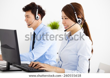 smiling business man and woman with headset working in office - stock photo