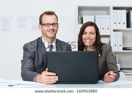 Smiling business man and woman working together as a team sitting at a table in the office sharing a laptop computer as they discuss a joint project - stock photo