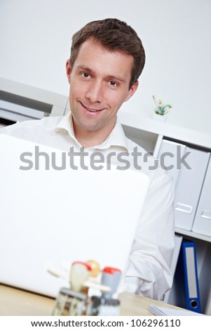Smiling business man at desk with laptop in the office - stock photo