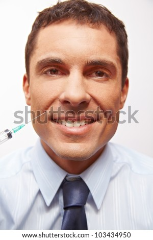 Smiling business man at wrinkle treatment getting needle in corner of mouth - stock photo