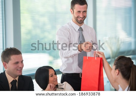 Smiling business man handing gift to female colleague - stock photo