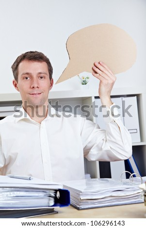 Smiling business man holding empty comic speech bubble