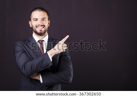 Smiling business man pointing at copy space against dark background - stock photo