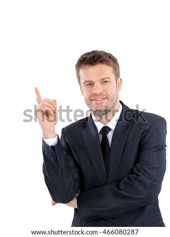 Smiling business man pointing on product or text.