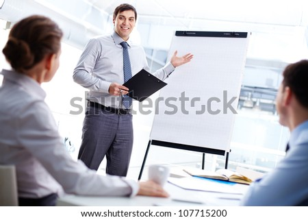 Smiling business man presenting his new strategy to the colleagues - stock photo