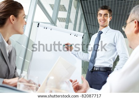 Smiling business man presenting new project to his partners on a whiteboard - stock photo