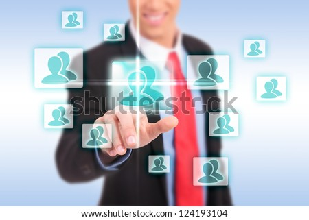 smiling business man pressing the add friend button on a social network virtual screen - stock photo