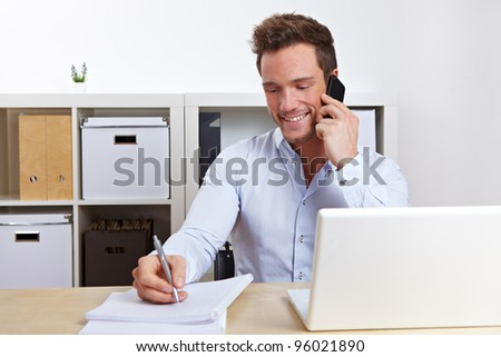 Smiling business man using cell phone at desk in office - stock photo