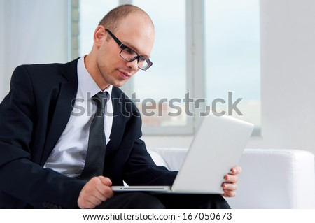 Smiling business man wearing glasses using a laptop in office