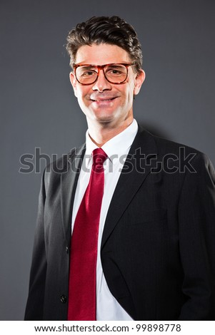 Smiling business man with grey suit and red tie isolated on dark background. Wearing retro glasses. Studio shot.