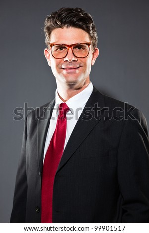 Smiling business man with grey suit and red tie isolated on dark background. Wearing vintage glasses. Studio shot.