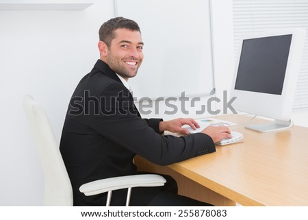 Smiling business man working at a desk in his office