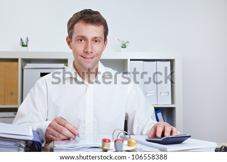 Smiling business man working at his desk in his office - stock photo