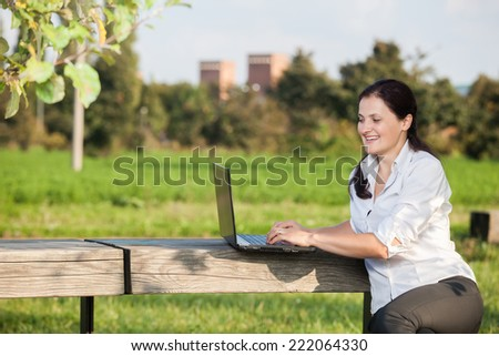 Smiling business mature woman writing on laptop sitting on the wooden table in the park - stock photo