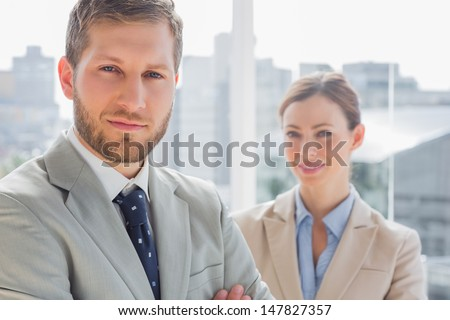 Smiling business partners looking at camera by large window
